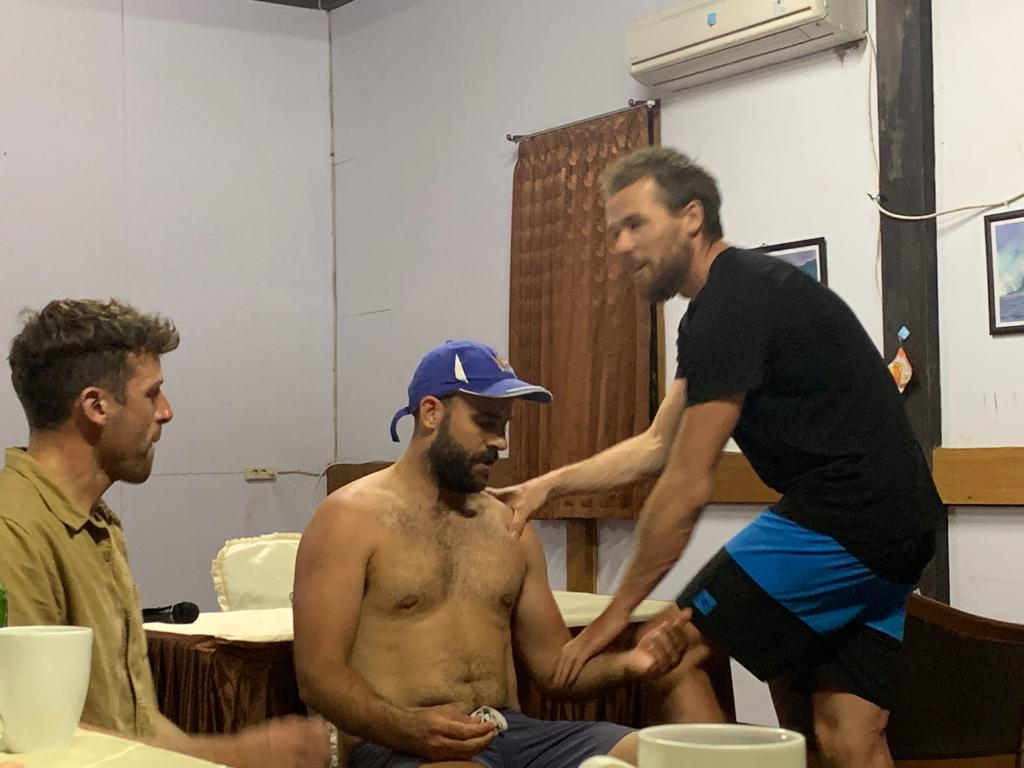 Emergency Consultant Dr Ant Buddle demonstrating the Cunningham Technique for shoulder relocation in the jungle with model patient Dr James CDent and Anaesthetics Consultant Dr Dennis Millard