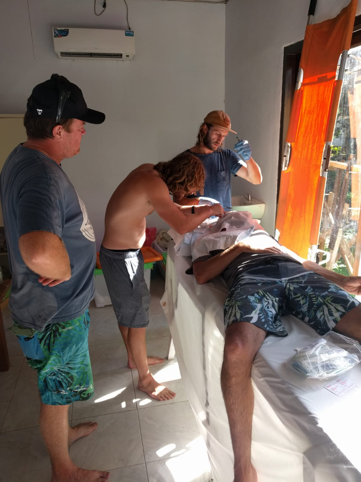 Jon Cohen and Jim Parko fixing up surf guide Hosko who took a fin to the head at G-:and